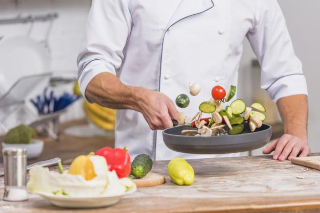 Μάγειρας με σακάκι chef μαγειρεύει λαχανικά