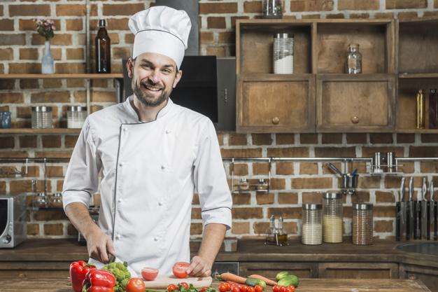 Όρθιος μάγειρας με λευκό σακάκι σεφ