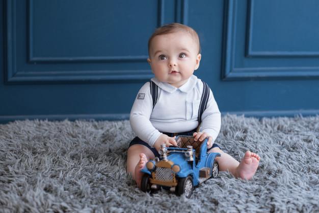 Ντυμένο νεογέννητο παιδί με παιχνίδι επάνω σε χαλί