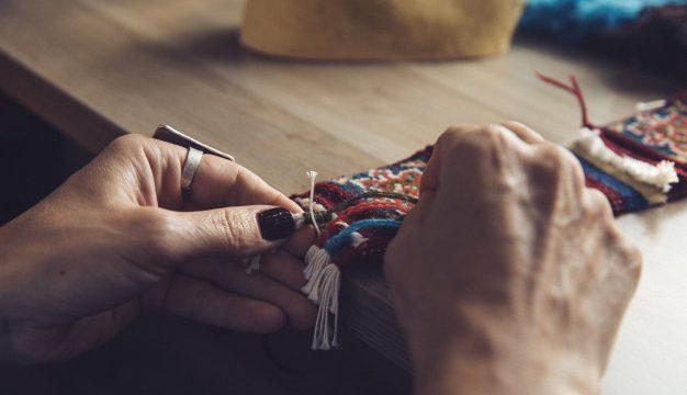 Γυναικεία χέρια υφαίνουν χαλί