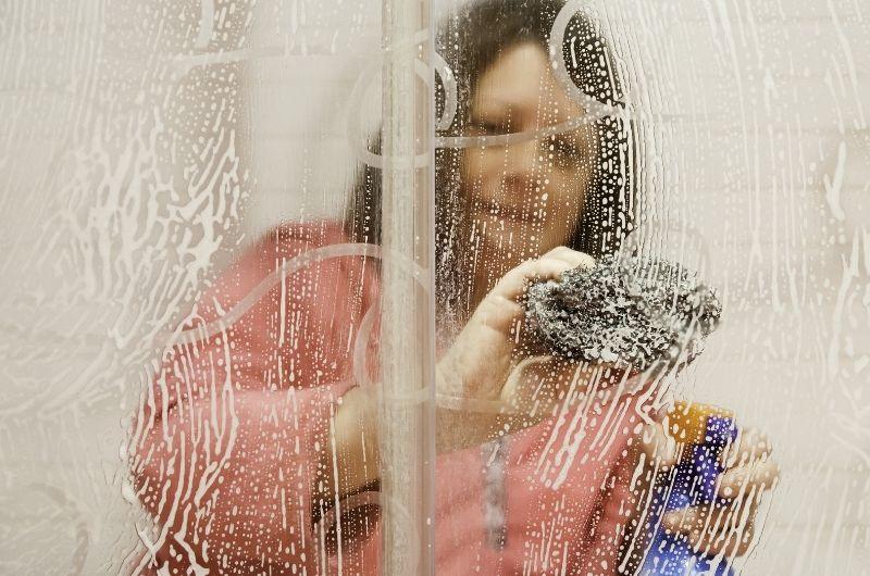 γυναίκα καθαρίζει ντουζιέρα