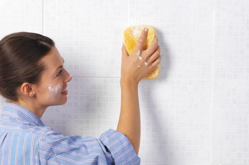 γυναίκα καθαρίζει πλακάκια μπάνιου