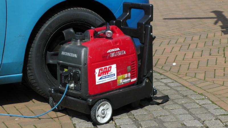 Κόκκινη γεννήτρια πετρελαίου Honda δίπλα σε αυτοκίνητο